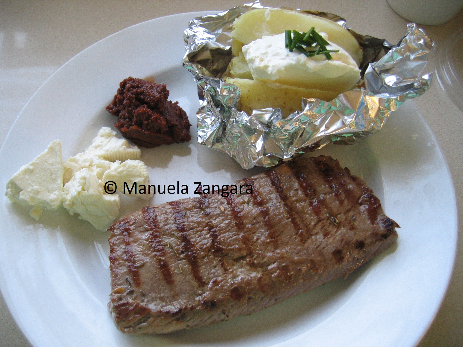 Lamb steak with sun dried tomatoes, feta and baked potato